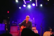 "Watch Josh Homme Play Unreleased Song ""Villains Of Circumstance"" At Benefit Show In LA"