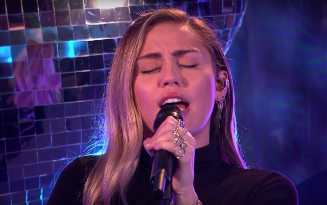 Miley Cyrus goes braless throughout her SNL efficiency